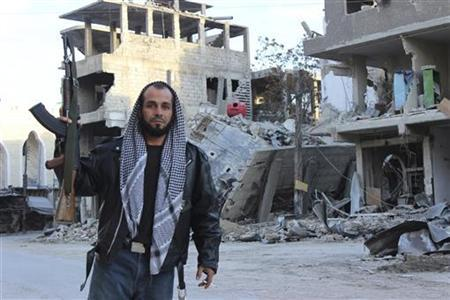 A Free Syrian Army fighter poses near buildings, damaged by what activists said were missiles fired by a Syrian Air Force fighter jet of forces loyal to Syrian President Bashar al-Assad, at Zamalka near Damascus December 19, 2012. REUTERS/Karm Seif/Shaam News Network/Handout