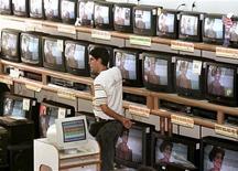 Um vendedor aguarda próximo a televisores em uma loja no Rio de Janeiro. 11/11/1997 REUTERS/Gregg Newton