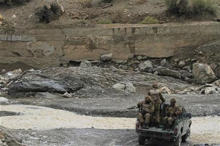 Pakistani soldiers drive through a stream during their patrol at Wana Jandola road near Wana November 28, 2012. REUTERS/Faisal Mahmood/Files