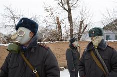 Милиционерв в противогазах патрулируют улицы селения Кара-Жигач в Киргизии 22 декабря 2009 года. Президент Киргизии пообещал продать обремененную долгами государственную газовую компанию российскому Газпрому в надежде ослабить убийственный для бедной страны энергетический кризис. REUTERS/Vladimir Pirogov