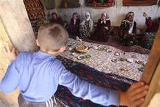 Мальчик смотрит в окно на сидящих в доме жительниц таджикского села Горная Мастча 9 июня 2008 года. Таджикистан в очередной раз заблокировал доступ к популярным в рунете социальным сетям, оппозиционным информресурсам и еще сотне сайтов, назвав это временной технической мерой, тогда как наблюдатели сочли это репетицией установления контроля над неподцензурными площадками в преддверии президентских выборов-2013. REUTERS/Nozim Kalandarov