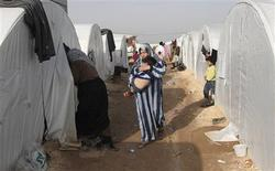 A Syrian refugee woman holds her child in the refugee camp of Bab El Salama, between the Syrian town of Azaz and the Turkish town of Kilis, December 24, 2012. REUTERS/Muzaffar Salman