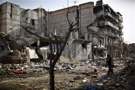 A fighter from Islamist Syrian rebel group Jabhat al-Nusra walks between damaged houses in Aleppo December 24, 2012. REUTERS/Ahmed Jadallah