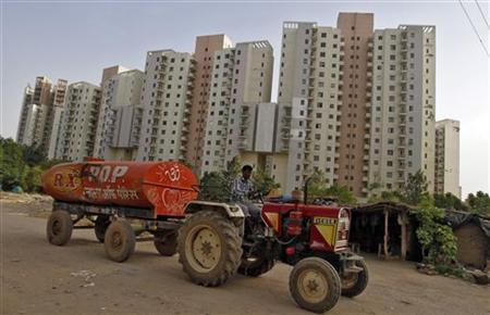 A water tanker moves past Malibu Towne residential apartments at Gurgaon, on the outskirts of New Delhi, June 16, 2012. REUTERS/Parivartan Sharma