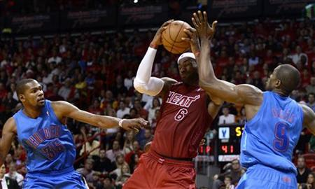Miami Heat's LeBron James (C) is defended by Oklahoma City Thunder's Kevin Durant (L) and Serge Ibaka (R) during the first half of their NBA basketball game in Miami, Florida, December 25, 2012. REUTERS/Rhona Wise