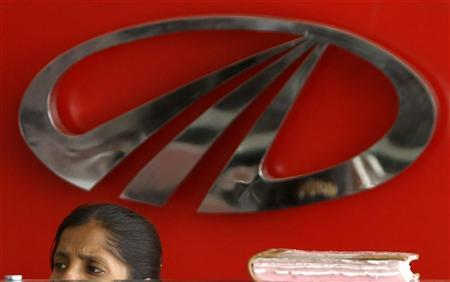 A worker sits in front of a logo of Mahindra & Mahindra, India's largest utility vehicles maker, inside their showroom in Chennai April 12, 2011. REUTERS/Babu/Files