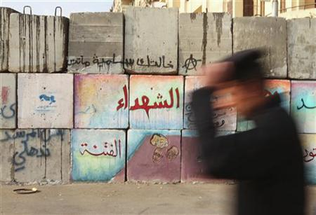 A policeman walks past a newly built up barrier to hold protesters away from the Egyptian presidential palace in Cairo December 25, 2012. REUTERS/Asmaa Waguih