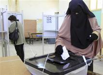 Женщина опускает бюллетень на избирательном участке в Суэце 22 декабря 2012 года. Египтяне одобрили новую конституцию страны, которую разработал президент-исламист Мохамед Мурси и его союзники, свидетельствуют обнародованные во вторник итоги референдума. REUTERS/Mohamed Abd El Ghany