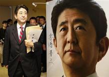 Избранный премьер-министр Японии Синдзо Абэ проходит мимо плаката со своим изображением во время встречи в штаб-квартире Либерально-демократической партии в Токио 21 декабря 2012 года. Нижняя палата японского парламента в среду утвердила Синдзо Абэ в качестве премьер-министра, дав ему второй шанс встать во главе страны, которая борется с экономическим кризисом и переживает ухудшение отношений с Китаем. REUTERS/Toru Hanai