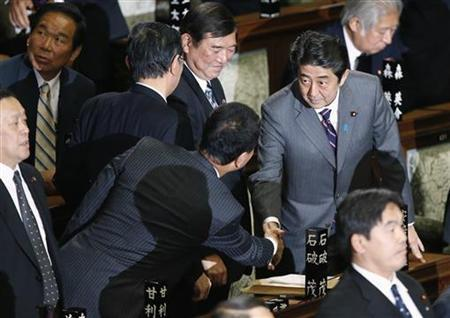 Japan's newly-elected Prime Minister Shinzo Abe (R) shakes hands with his party members after he was chosen as the new prime minister at the Lower House of Parliament in Tokyo December 26, 2012. REUTERS/Toru Hanai