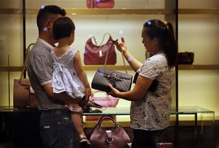 A woman shops for handbags at a Gucci luxury boutique at the IFC Mall in Shanghai June 4, 2012. REUTERS/Carlos Barria