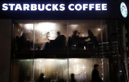 Customers are seen behind the steamy windows of a Starbucks coffee house in central London December 20, 2012. REUTERS/Chris Helgren