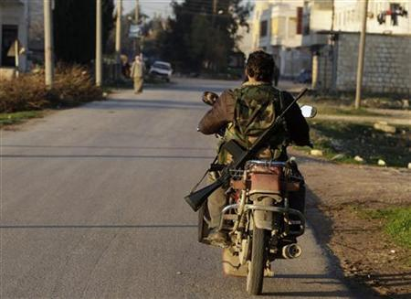 A Free Syrian Army fighter rides his motorcycle outside Azaz city in north Aleppo December 26, 2012. REUTERS/Ahmed Jadallah