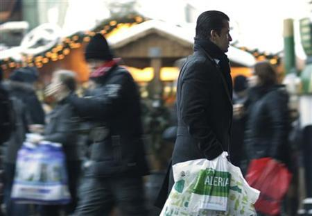 People carry shopping bags outside the Alexa retail centre in Berlin, December 19, 2010. Many retailers in Germany are open this Sunday due to Christmas shopping season. REUTERS/Thomas Peter (GERMANY - Tags: SOCIETY)