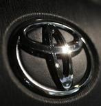Логотип Toyota на руле модели Prius в демонстрационном зале в Токио 23 октября 2012 года. Toyota Motor Corp планирует потратить $1,1 миллиарда на урегулирование судебного разбирательства по поводу случаев непроизвольного ускорения миллионов автомобилей в США. REUTERS/Kim Kyung-Hoon