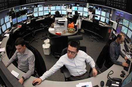 Traders are pictured at their desks at the Frankfurt stock exchange February 14, 2012. REUTERS/Alex Domanski/Files