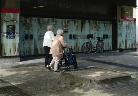 Elderly women walk past an empty warehouse in the western city of Herten September 11, 2012. Picture taken on September 11, 2012. REUTERS/Ina Fassbender