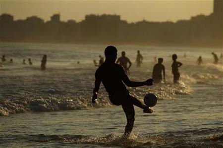 A man kicks a ball at the Copacabana beach in Rio de Janeiro December 25, 2012. REUTERS/Pilar Olivares
