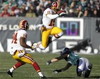 Washington Redskins receiver Joshua Morgan (15) leaps to avoid a tackle from Philadelphia Eagles safety Colt Anderson (30) as Redskins' Niles Paul (84) follows the play during the second quarter of their NFL football game in Philadelphia, Pennsylvania, December 23, 2012. REUTERS/Tim Shaffer