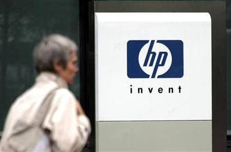A woman walks past the Hewlett Packard logo at its French headquarters in Issy le Moulineaux, western Paris, in this September 16, 2005 file photograph. EUTERS/Charles Platiau/Files