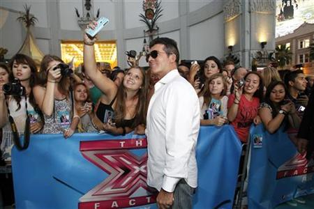 Simon Cowell poses with a fan at the season two premiere of the television series ''The X Factor'' at Grauman's Chinese theatre in Hollywood, California September 11, 2012. REUTERS/Mario Anzuoni/Files