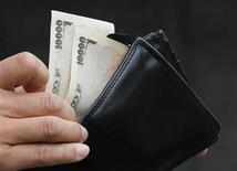Человек вынимает из кошелька две купюры валюты иена у банка в Токио 22 ноября 2012 года. Курс иены к доллару упал до более чем двухлетнего минимума из-за ожиданий, что новое правительство Японии будет настаивать на более активном смягчении политики центробанка. REUTERS/Kim Kyung-Hoon