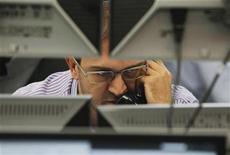 """Трейдер в торговом зале Тройки Диалог в Москве 26 сентября 2011 года. Рубль подешевел при открытии торгов пятницы, на дальнейшую динамику последней валютной сессии 2012 года будут влиять внутренние денежные потоки, а также спекуляции вокруг предстоящего возобновления переговоров по недопущению """"бюджетного обрыва"""" в США. REUTERS/Denis Sinyakov"""
