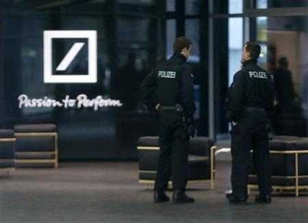 Police officers stand inside the lobby of the headquarters of Germany's largest business bank, Deutsche Bank AG in Frankfurt December 12, 2012. REUTERS/Kai Pfaffenbach