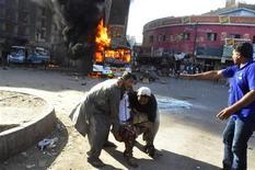 Pessoas tiram homem ferido de área de explosão na região de Cantonment, Karachi, Paquistão. Uma bomba explodiu em um ônibus na cidade paquistanesa de Karachi neste sábado, matando seis pessoas e ferindo 48, informou a polícia e um funcionário de hospital da cidade. 29/12/2012 REUTERS/Stringer