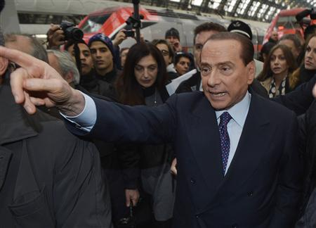 Former Italian Prime Minister Silvio Berlusconi gestures as he arrives at Milan train station December 29, 2012. REUTERS/Paolo Bona