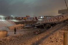 """На полученной Рейтер от очевидца фотографии - обломки самолета рядом с автомагистралью около аэропорта """"Внуково"""" под Москвой 29 декабря 2012. Водяной знак поставлен на оригинале фото. Четверо из примерно десятка человек на борту погибли в результате выкатывания самолёта Ту-204 на Киевское шоссе при посадке в московском аэропорту """"Внуково"""", втором подобном инциденте за неделю, сообщили власти. REUTERS/Alexander Usoltsev/Handout"""