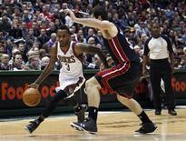 Brandon Jennings (en blanc) des Bucks tente de se frayer un passage face à Josh Harrellson du Heat. Les Bucks de Milwaukee ont assommé samedi le Miami Heat par 104 points à 85, infligeant au champion en titre de la NBA une seconde défaite consécutive. /Photo prise le 29 décembre 2012/REUTERS/Darren Hauck