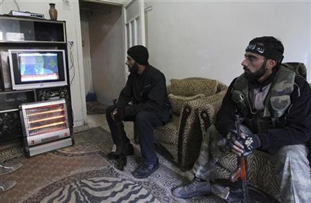 Free Syrian Army Fighters watch Russia's Foreign Minister Sergei Lavrov on TV at a house in Aleppo December 29, 2012. REUTERS/Muzaffar Salman (SYRIA - Tags: CONFLICT POLITICS)