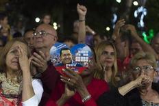 """El presidente venezolano, Hugo Chávez, pasó el día """"tranquilo y estable"""", aseguró el lunes el ministro de Ciencia y Tecnología, Jorge Arreaza, quien está en Cuba junto al líder socialista que convalece de una cuarta operación por un cáncer que ha levantado dudas sobre si podrá seguir al mando del país petrolero. En la imagen, partidarios de Chávez en una ceremonia en su honor, en Caracas, el 31 de diciembre de 2012. REUTERS/Carlos Garcia Rawlins"""