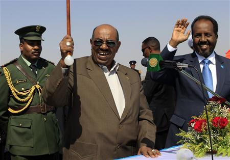 Sudan's President Omar Hassan al-Bashir (C) waves next to Somali President Hassan Sheikh Mohamud (R) after signing a document to signal the start of operations during the inauguration of the Roseires Dam's height increase in Damazin, at the conflict-stricken Blue Nile state, January 1, 2013. REUTERS/Mohamed Nureldin Abdallah
