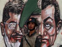 Membro da guarda republicana é visto próximo a parede com grafite retratando o presidente egípcio Mohamed Mursi (E) e o ex-presidente Hosni Mubarak (D), no Cairo. Um humorista egípcio que fez piadas sobre Mursi na televisão foi acusado de enfraquecer a posição do líder e será investigado por promotores, afirmou uma fonte ligada à Justiça nesta terça-feira. 18/12/2012 REUTERS/Mohamed Abd El Ghany