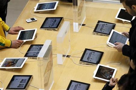 Customers look at Apple's new iPad 4G-ready tablet computers at one of their stores in Paris March 16, 2012. REUTERS/Charles Platiau/Files