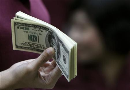 An employee working as a money changer prepares U.S. dollar currency for a customer in Jakarta October 28, 2008. REUTERS/Enny Nuraheni/Files