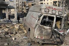 Moradores caminham próximo à ambulância destruída em Aleppo, Síria. Rebeldes sírios, alguns de unidades islamistas, dispararam tiros de metralhadora e morteiros contra helicópteros parados em uma base aérea militar no norte, perto da principal rodovia que liga Aleppo a Damasco, nesta quarta-feira, disse um grupo de monitoramento. 01/01/2013 REUTERS/Muzaffar Salman