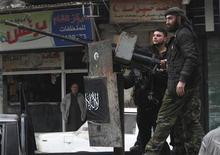 Unos integrantes del Ejército de Siria Libre detrás de un arma automática durante una patrulla en el distrito Bustan Al Qaser en Aleppo, ene 2 2013. Más de 60.000 personas han muerto en Siria desde que empezó la revuelta que desencadenó una guerra civil, dijo el miércoles Naciones Unidas, al elevar dramáticamente la cifra estimada de víctimas fatales en momentos en que no hay señales de tregua a la vista. REUTERS/Muzaffar Salman