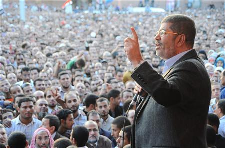Egypt's President Mohamed Mursi speaks to supporters in front of the presidential palace in Cairo November 23, 2012. REUTERS/Egyptian Presidency/Handout
