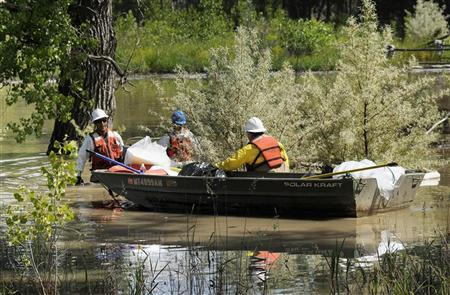 Emergency response crew hired by Exxon Mobil clean up oil spill along the Yellowstone River in Laurel, Montana, July 6, 2011. REUTERS/John Warner