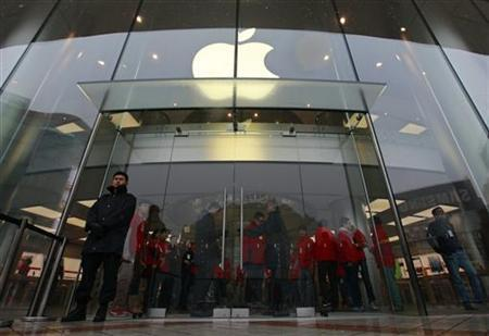 Security guards and staff stand at the entrance of an Apple store during the release of iPhone 5 in Beijing's Wangfujing shopping district, December 14, 2012. REUTERS/Petar Kujundzic (CHINA - Tags: BUSINESS TELECOMS)