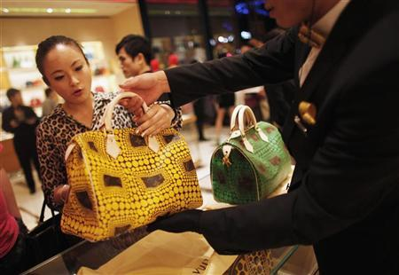 A woman shops in a Louis Vuitton store during Vogue's 4th Fashion's Night Out: Shopping Night with Celebrities in downtown Shanghai September 7, 2012. REUTERS/ Carlos Barria