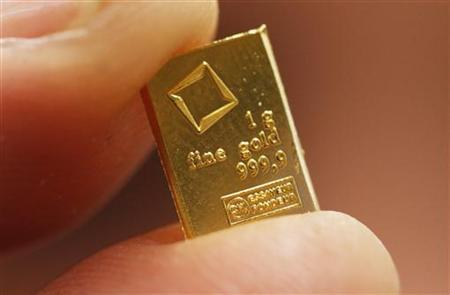 An employee shows a 1 gram piece of a gold Combibar at a plant of gold refiner and bar manufacturer Valcambi SA in the southern Swiss town of Balerna December 20, 2012. REUTERS/Michael Buholzer