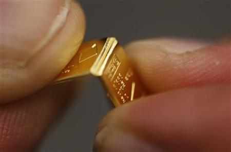 An employee shows dividing a gold Combibar at a plant of gold refiner and bar manufacturer Valcambi SA in the southern Swiss town of Balerna December 20, 2012. REUTERS/Michael Buholzer