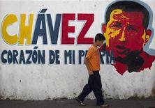 """El mandatario venezolano Hugo Chávez sufre una insuficiencia respiratoria como consecuencia de la infección pulmonar """"severa"""" que padece, dijo el jueves el Gobierno, en una nueva complicación tras la operación a la que fue sometido hace tres semanas en Cuba por un cáncer que amenaza con alejarlo del poder. En la imagen, un niño pasa frente a una pintura de Chávez en Caracas, el 3 de enero de 2013. REUTERS/Carlos García Rawlins"""