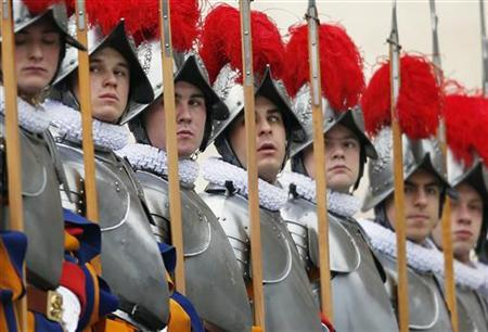 Swiss guards stand before Pope Benedict XVI arrives for his ''Urbi et Orbi'' (To the city and the world) address from a balcony in St. Peter's Square in Vatican December 25, 2012. REUTERS/Alessandro Bianchi (VATICAN - Tags: RELIGION TPX IMAGES OF THE DAY)