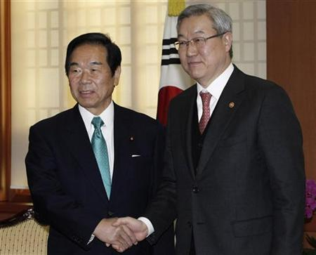 Fukushiro Nukaga (L), the special envoy of Japanese Prime Minister Shinzo Abe, shakes hands with South Korean Foreign Minister Kim Sung-hwan during their meeting at Kim's office in Seoul January 4, 2013. REUTERS/Ahn Young-joon/Pool