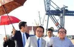 Taro Aso (au centre) en visite dans le port de Thilawa, dans la banlieue de Rangoun, en Birmanie. Le vice-premier ministre japonais a confirmé vendredi le déblocage d'une aide financière pour la Birmanie, nouvelle terre d'opportunités pour les entreprises nippones, lors de son premier déplacement officiel à l'étranger depuis sa prise de fonction. /Photo prise le 4 janvier 2013/REUTERS